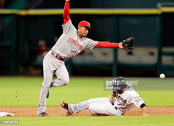 Jose Altuve of the Houston Astros slides safely into second base as Wilson Valdez of the Cincinnati Reds can't reach the wide throw at Minute Maid...