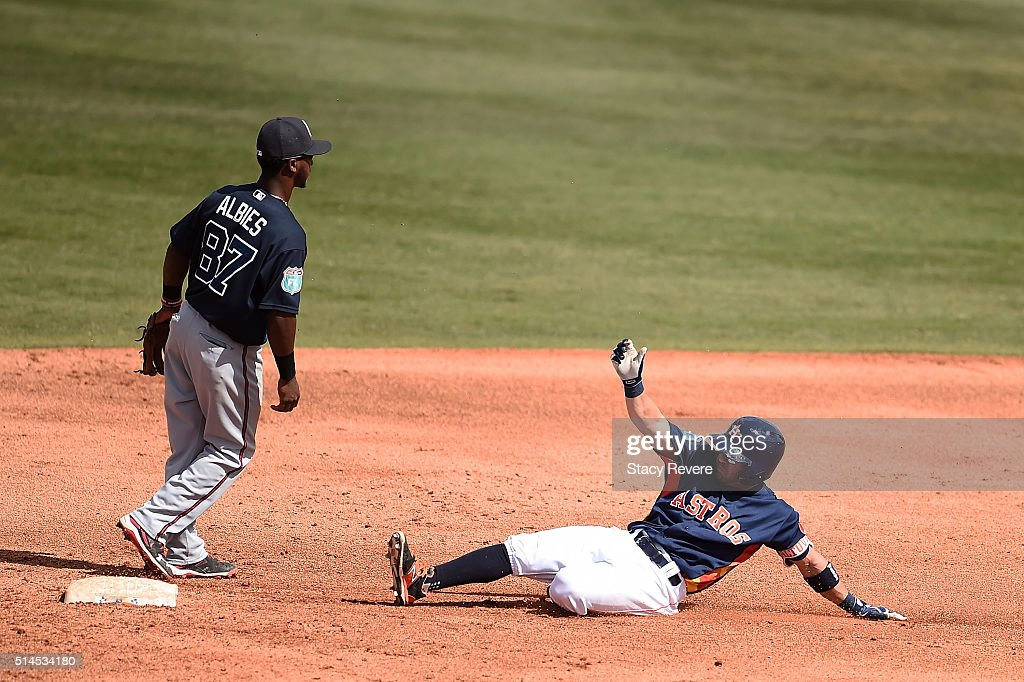 Jose Altuve #27 of the Houston Astros slides safely into second base during the fourth inning of a spring training game against the Atlanta Braves at Osceola County Stadium on March 9, 2016 in Kissimmee, Florida.