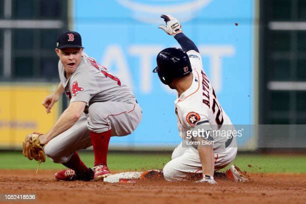 Jose Altuve of the Houston Astros slides safely into second base with a double as Brock Holt of the Boston Red Sox applies the tag in the third...