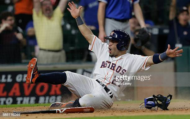 Jose Altuve of the Houston Astros slides to score the wining run in the fourteenth inning at Minute Maid Park on August 1, 2016 in Houston, Texas.