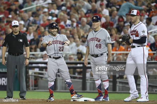 Jose Altuve of the Houston Astros stands on first base with Freddie Freeman of the Atlanta Braves during the 89th MLB AllStar Game presented by...