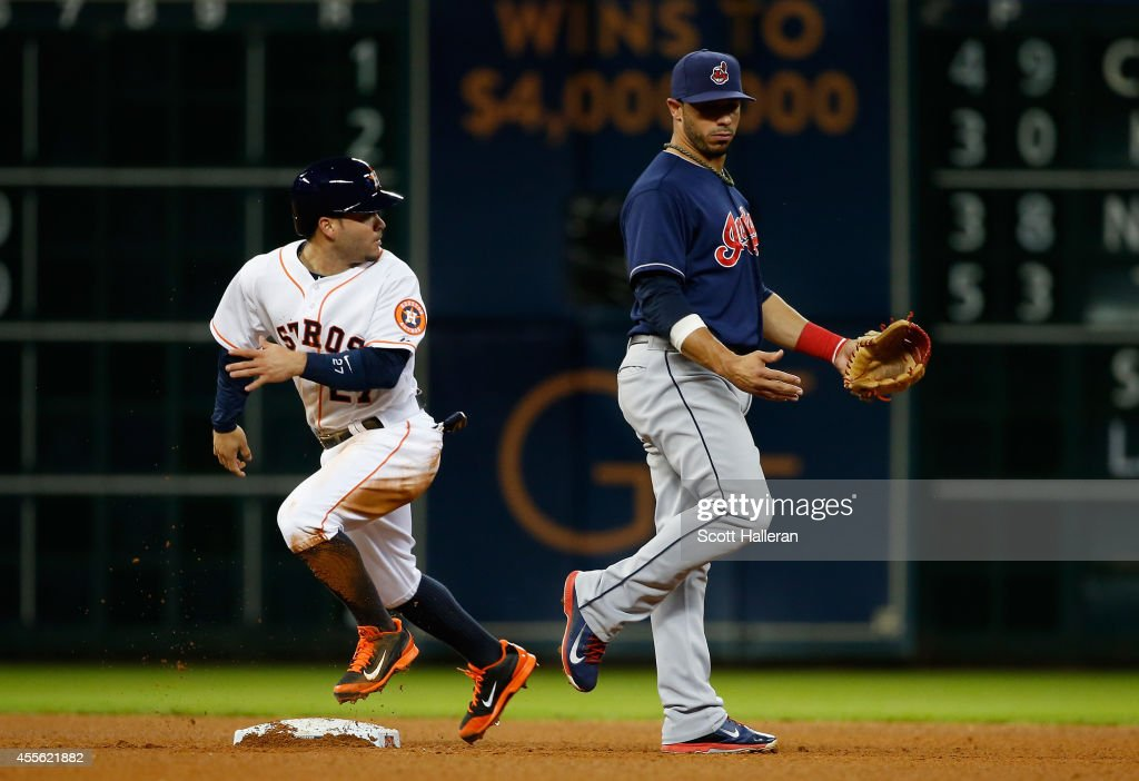 Jose Altuve #27 of the Houston Astros steals second base as Mike Aviles #4 of the Cleveland Indians looks on during the fourth inning of their game at Minute Maid Park on September 17, 2014 in Houston, Texas.