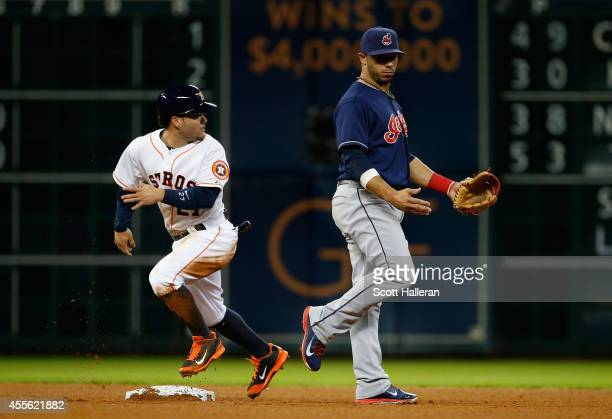 Jose Altuve of the Houston Astros steals second base as Mike Aviles of the Cleveland Indians looks on during the fourth inning of their game at...