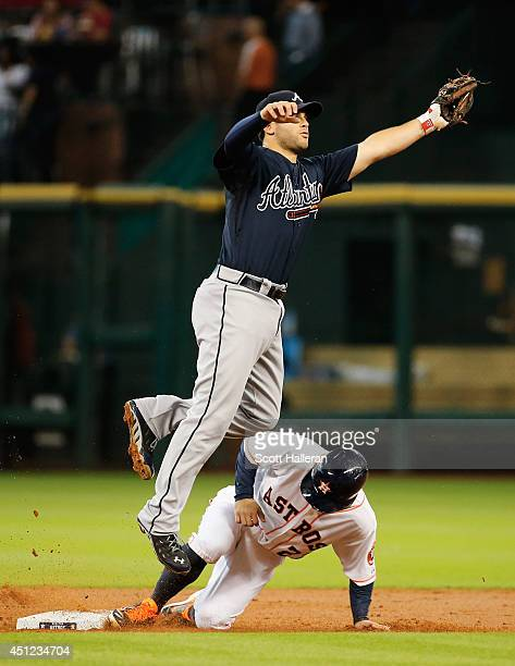 Jose Altuve of the Houston Astros steals second base under the tag of Tommy La Stella of the Atlanta Braves during the first inning of their game at...