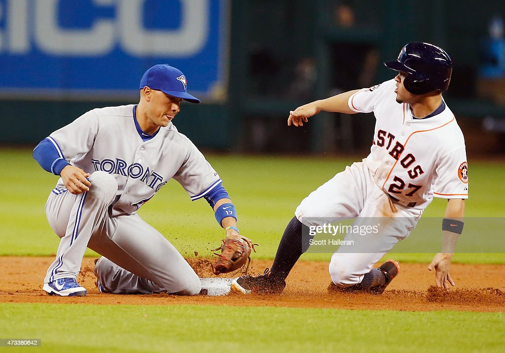 Jose Altuve #27 of the Houston Astros steals second base under the tag of Ryan Goins #17 of the Toronto Blue Jays in the first inning of their game at Minute Maid Park on May 14, 2015 in Houston, Texas.