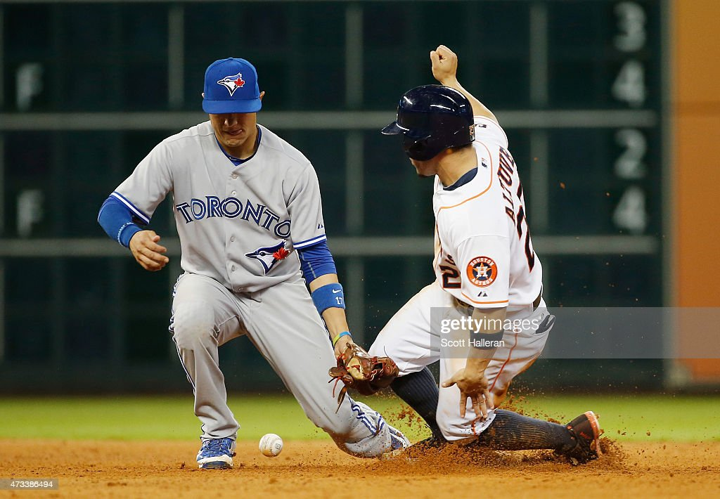 Jose Altuve #27 of the Houston Astros steals second base under the tag of Ryan Goins #17 of the Toronto Blue Jays in the seventh inning of their game at Minute Maid Park on May 14, 2015 in Houston, Texas.