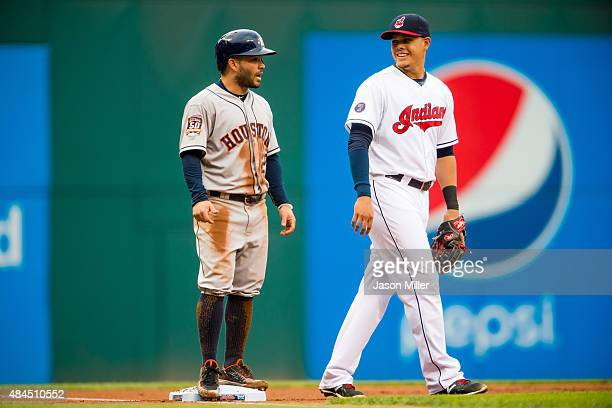 Jose Altuve of the Houston Astros talks to third baseman Giovanny Urshela of the Cleveland Indians on third base during the first inning at...