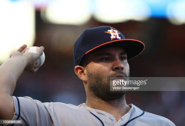 Jose Altuve of the Houston Astros throws a ball to a fan as he walks back to the dugout after the first inning of the MLB game against the Los...