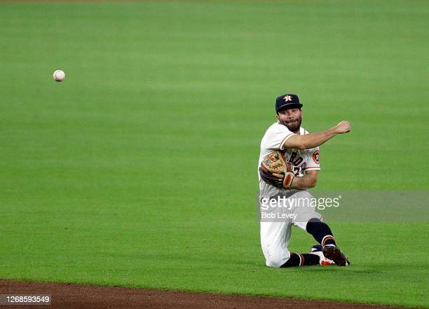 Jose Altuve of the Houston Astros throws falling backwards to retire Anthony Bemboom of the Los Angeles Angels in the third inning during game two of...
