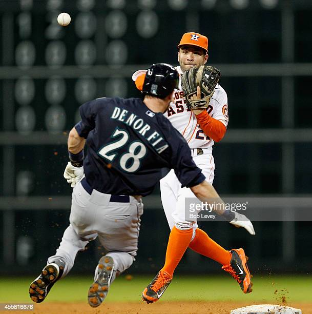 Jose Altuve of the Houston Astros throws over Chris Denorfia of the Seattle Mariners to complete a double play in the fifth inning at Minute Maid...
