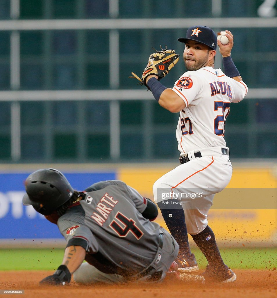 Jose Altuve #27 of the Houston Astros throws over Ketel Marte #4 of the Arizona Diamondbacks to complete a double play in the sixth inning at Minute Maid Park on August 17, 2017 in Houston, Texas.