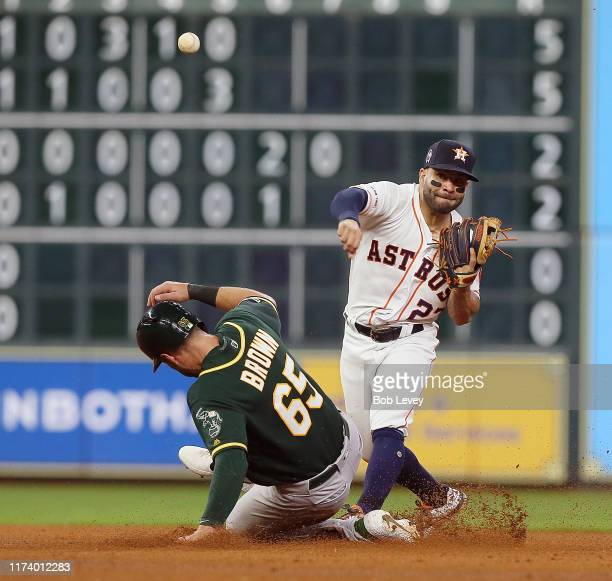 Jose Altuve of the Houston Astros throws over Seth Brown of the Oakland Athletics to complete a double play in the fifth inning at Minute Maid Park...