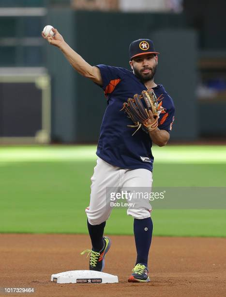 Jose Altuve of the Houston Astros throws to first base during infield practice before a baseball game against the Colorado Rockies at Minute Maid...