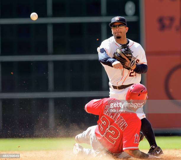 Jose Altuve of the Houston Astros throws to first base over a sliding Josh Hamilton of the Los Angeles Angels of Anaheim but was unable to get the...