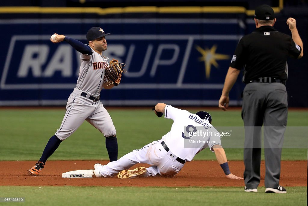 Jose Altuve #27 of the Houston Astros turns a double play as Jake Bauers #9 of the Tampa Bay Rays slides into second during a game at Tropicana Field on June 29, 2018 in St Petersburg, Florida.
