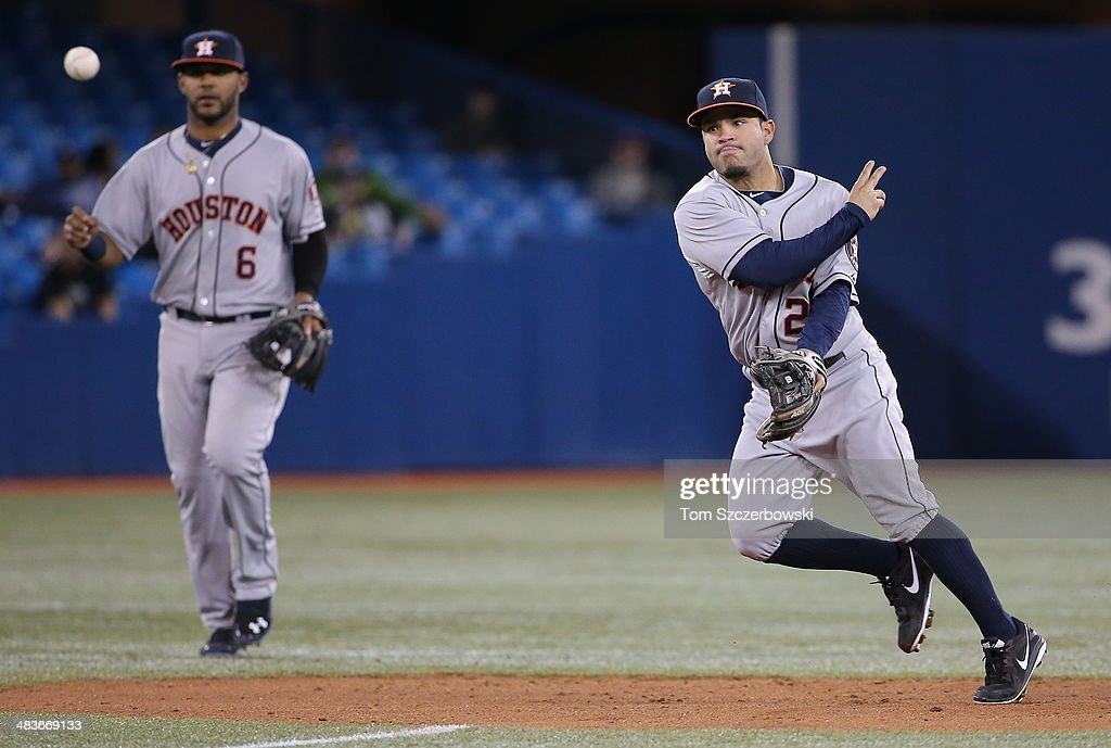 Jose Altuve #27 of the Houston Astros turns a double play in the eighth inning as Jonathan Villar #6 looks on during MLB game action against the Toronto Blue Jays on April 9, 2014 at Rogers Centre in Toronto, Ontario, Canada.