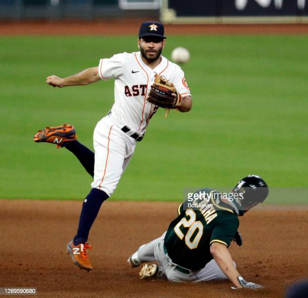 Jose Altuve of the Houston Astros turns a double play in the sixth inning as he throws to first base over Mark Canha of the Oakland Athletics during...