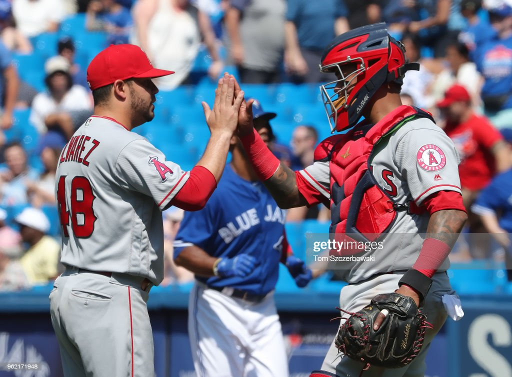 Jose Alvarez #48 of the Los Angeles Angels of Anaheim celebrates their victory with Martin Maldonado #12 during MLB game action against the Toronto Blue Jays at Rogers Centre on May 24, 2018 in Toronto, Canada.