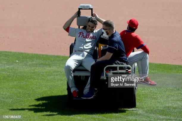 Jose Alvarez of the Philadelphia Phillies reacts while being carted off the field after being hit by a ball during the fifth inning of game one of a...