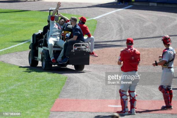 Jose Alvarez of the Philadelphia Phillies waves while being carted off the field after being hit by a ball during the fifth inning of game one of a...