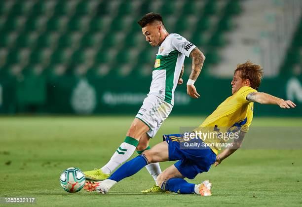 Jose Antonio Ferrandez Pomares of Elche CF competes for the ball with Alex Fernandez Iglesias of Cadiz CF during the La Liga Smartbank match between...