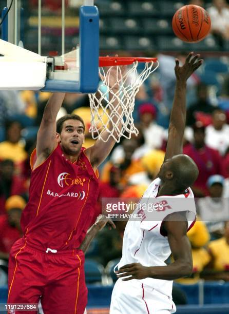 Jose Antonio Paraiso of Spain leaps to grab a pass as Eduardo Mingas of Angola guards 31 August 2002 during the second half of their preliminary...