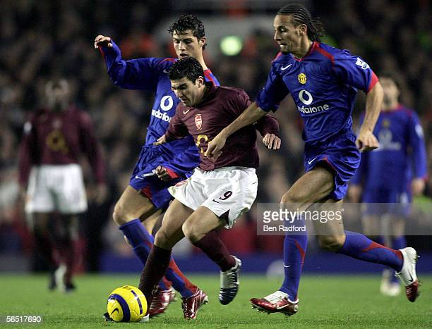 Jose Antonio Reyes of Arsenal goes between Cristiano Ronaldo and Rio Ferdinand of Manchester United during the Barclays Premiership match between...