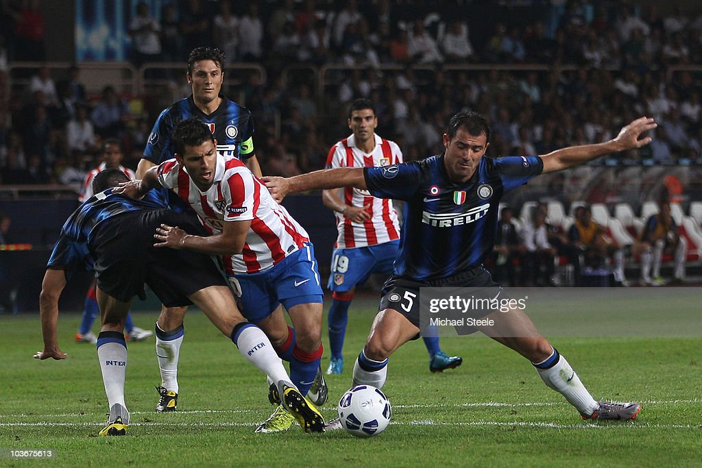 Jose Antonio Reyes (c) of Atletico is squeezed out by Dejan Stankovic (r) and Lucio (l) during the UEFA Super Cup match between Inter Milan and Atletico Madrid at Louis II Stadium on August 27, 2010 in Monaco, Monaco.