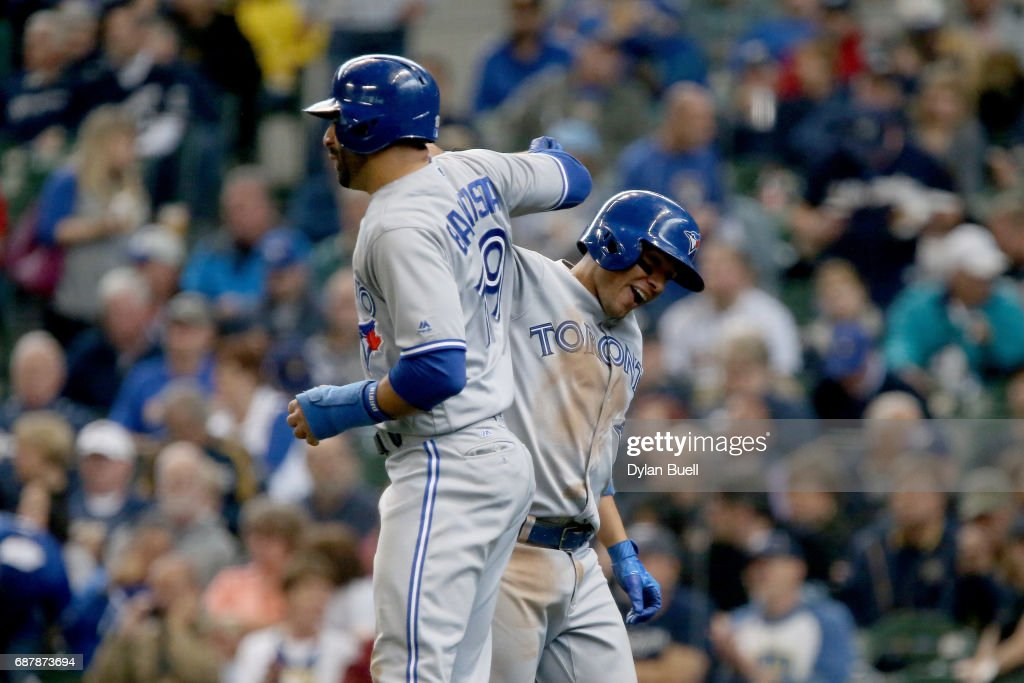 Jose Bautista #19 and Ryan Goins #17 of the Toronto Blue Jays celebrate after Goins hit a grand slam in the sixth inning against the Milwaukee Brewers at Miller Park on May 24, 2017 in Milwaukee, Wisconsin.