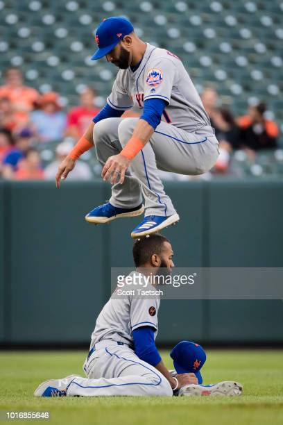 Jose Bautista of the New York Mets leaps over teammate Amed Rosario during warmups before the game against the Baltimore Orioles at Oriole Park at...