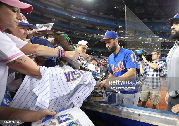 Jose Bautista of the New York Mets signs autographs for fans before the start of MLB game action against the Toronto Blue Jays at Rogers Centre on...
