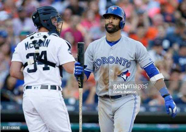 Jose Bautista of the Toronto Blue Jays and catcher James McCann of the Detroit Tigers head for their dugouts after Bautista strikes out to end the...