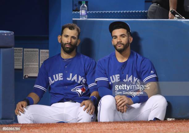 Jose Bautista of the Toronto Blue Jays and Devon Travis look on from the top step of the dugout during MLB game action against the New York Yankees...