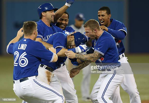 Jose Bautista of the Toronto Blue Jays celebrates his gamewinning hit in the tenth inning with Brett Lawrie during MLB game action against the Tampa...