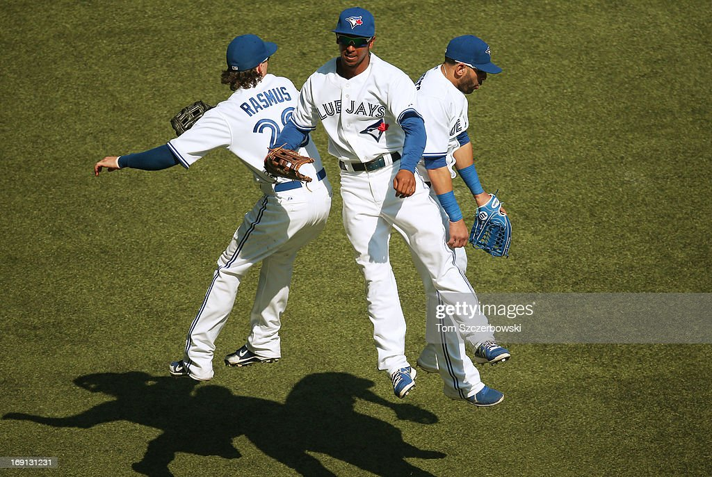 Jose Bautista #19 of the Toronto Blue Jays celebrates their victory with Colby Rasmus #28 and Anthony Gose #8 during MLB game action against the Tampa Bay Rays on May 20, 2013 at Rogers Centre in Toronto, Ontario, Canada.