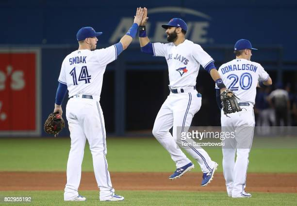 Jose Bautista of the Toronto Blue Jays celebrates their victory with Justin Smoak during MLB game action against the Baltimore Orioles at Rogers...