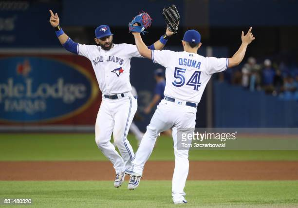 Jose Bautista of the Toronto Blue Jays celebrates their victory with Roberto Osuna during MLB game action against the Tampa Bay Rays at Rogers Centre...