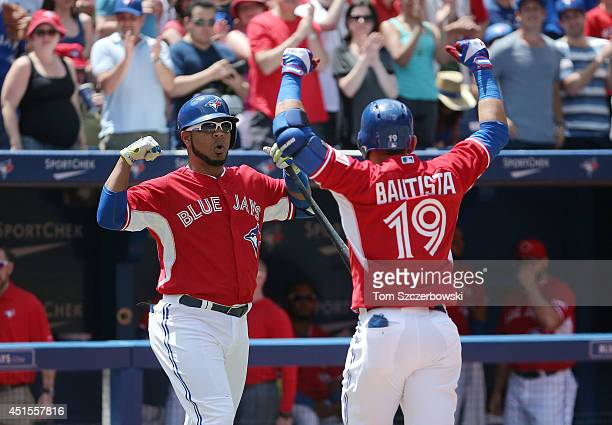 Jose Bautista of the Toronto Blue Jays celebrates with Edwin Encarnacion after hitting a solo home run in the first inning during MLB game action...