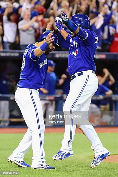 Jose Bautista of the Toronto Blue Jays celebrates with Edwin Encarnacion of the Toronto Blue Jays after they both score runs in the sixth inning...