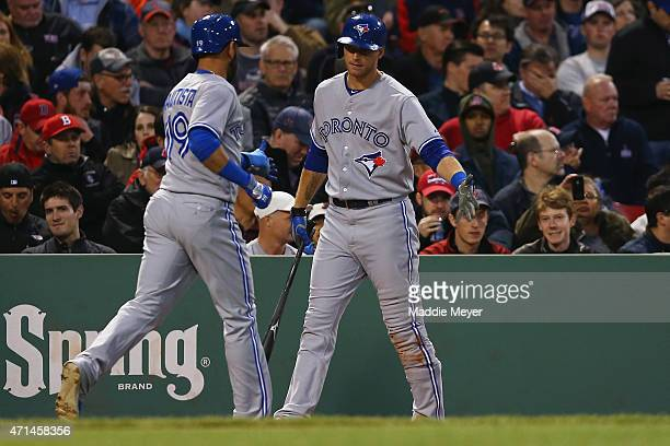 Jose Bautista of the Toronto Blue Jays celebrates with Michael Saunders after scoring a run against the Boston Red Sox during the fourth inning at...