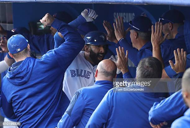 Jose Bautista of the Toronto Blue Jays celebrates with teammates in the dugout after hitting a threerun home run in the eighth inning during MLB game...
