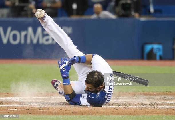 Jose Bautista of the Toronto Blue Jays falls after being knocked down by a high and inside fastball thrown by Zach McAllister of the Cleveland...
