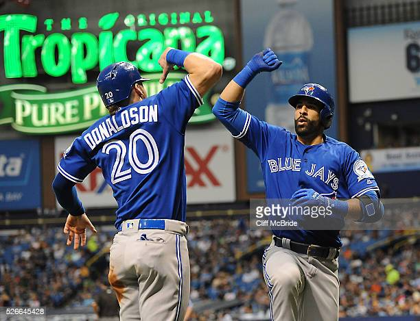 Jose Bautista of the Toronto Blue Jays high fives Josh Donaldson of the Toronto Blue Jays after his home run in the third inning against Tampa Bay...