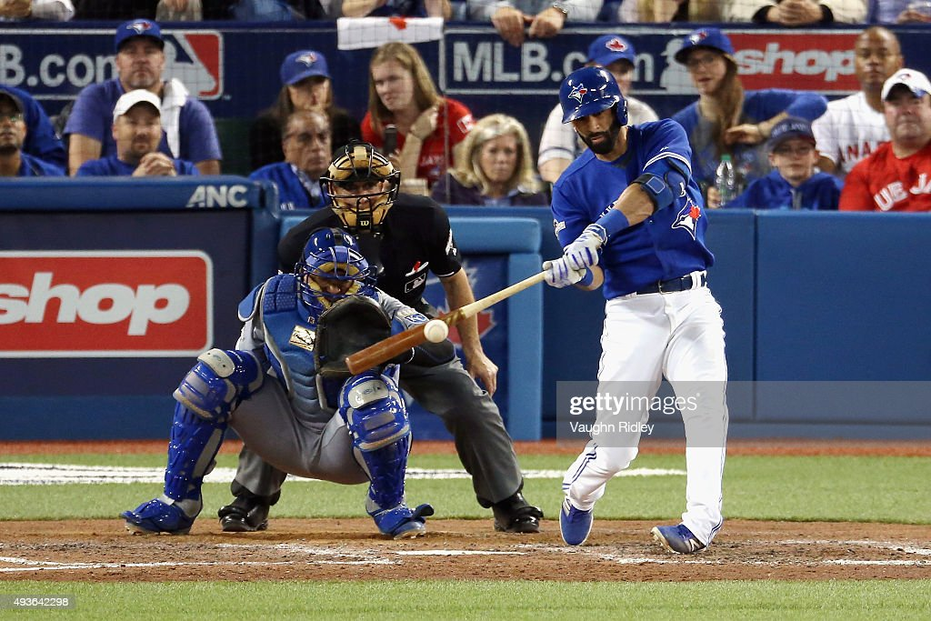 Jose Bautista #19 of the Toronto Blue Jays hits a double in front of Salvador Perez #13 of the Kansas City Royals to score Josh Donaldson #20 in the seventh inning during game five of the American League Championship Series at Rogers Centre on October 21, 2015 in Toronto, Canada.