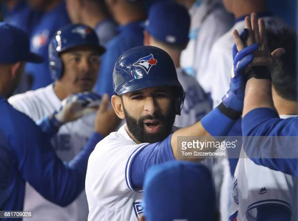 Jose Bautista of the Toronto Blue Jays is congratualted by teammates in the dugout after hitting a threerun home run in the first inning during MLB...