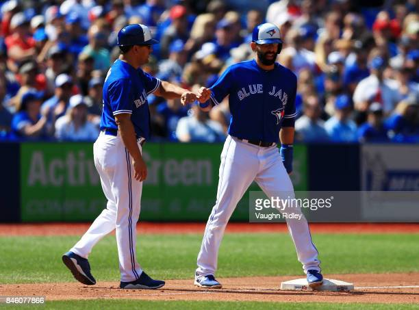 Jose Bautista of the Toronto Blue Jays is congratulated by 3rd base coach Luis Rivera after making his way to third during MLB game action against...