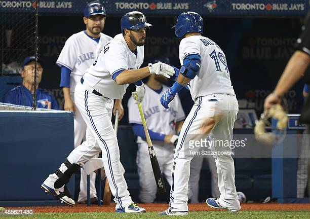 Jose Bautista of the Toronto Blue Jays is congratulated by Chris Colabello after hitting a solo home run in the fifth inning during MLB game action...