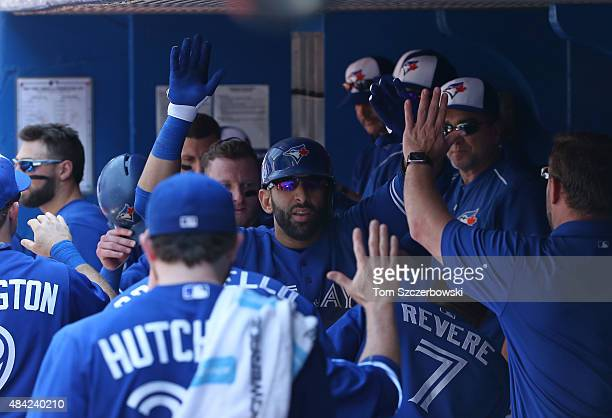 Jose Bautista of the Toronto Blue Jays is congratulated by Drew Hutchison and teammates in the dugout after hitting a tworun home run in the third...