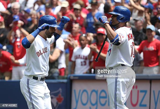Jose Bautista of the Toronto Blue Jays is congratulated by Edwin Encarnacion after hitting a tworun home run in the second inning during MLB game...