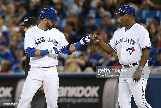 Jose Bautista of the Toronto Blue Jays is congratulated by first base coach Dwayne Murphy after hitting a single in the ninth inning during MLB game...